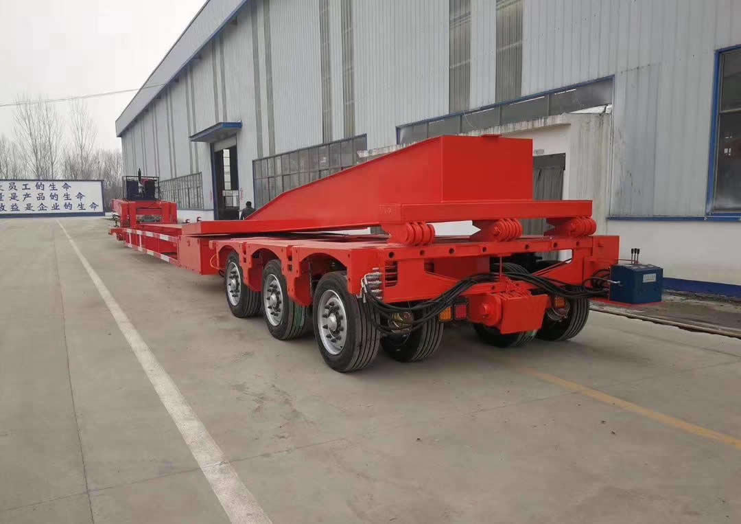 A folding extension beam at rear of a hydraulic multi-axle trailer