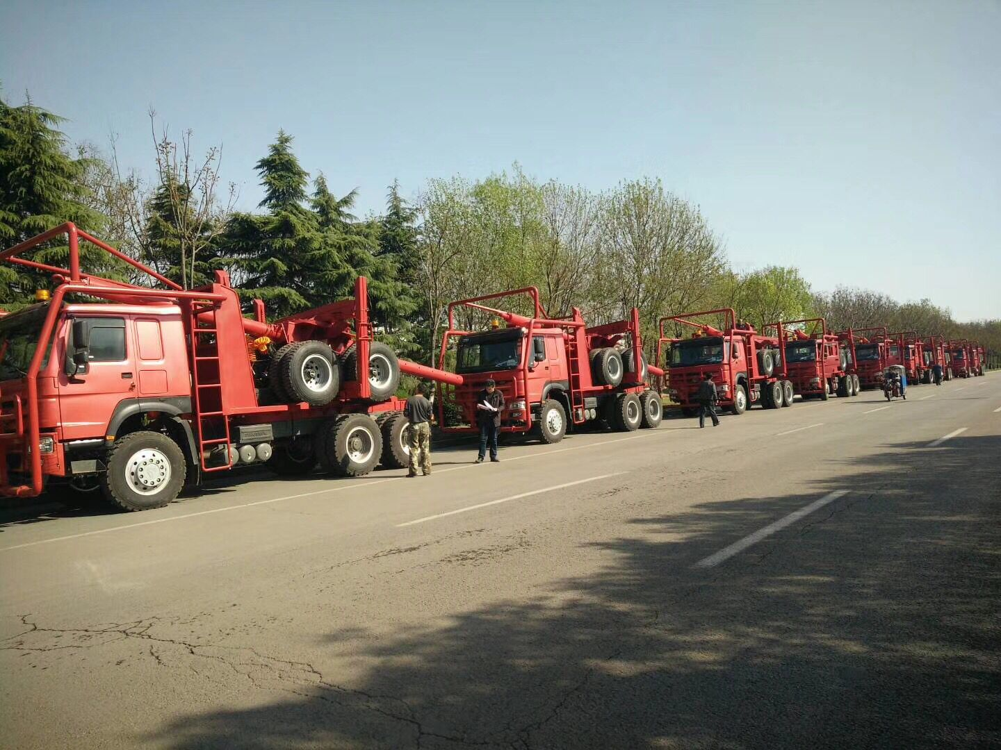 Red color log trailers waiting for delivery
