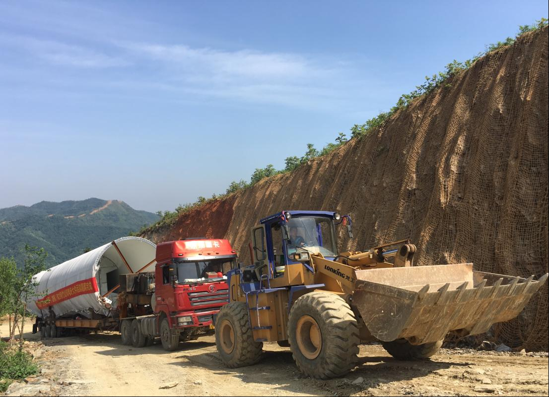 A loader helps to tow the windmill tower to the mountainous district
